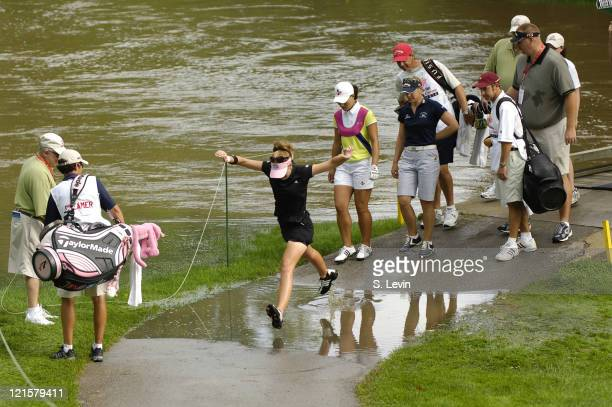 Paula Creamer leaps over one of the many submerged pathways during the first round of the Jamie Farr Owens Corning Classic at Highland Meadows Golf...