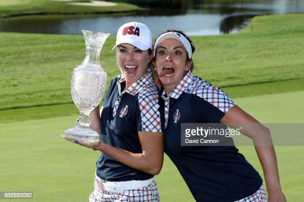 Paula Creamer of the United States Team holds the Solheim Cup as Gerina Piller enjoys a fun moment after the closing ceremony during the final day...