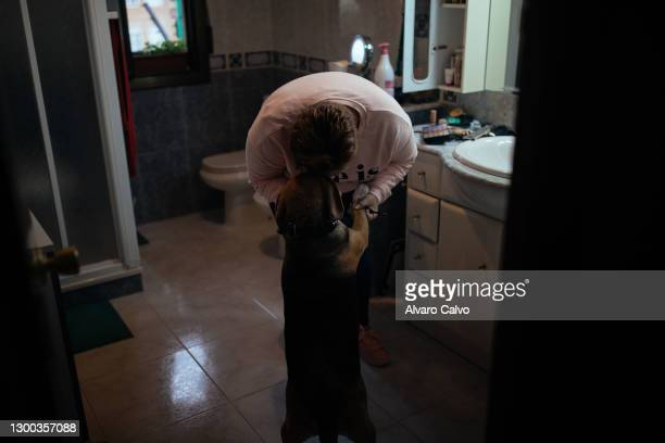 Paula Fernandez, pets her dog at her home on November 4, 2020 in Tamarite de Litera, Spain. Paula is a mother of two children. Two years ago she was...