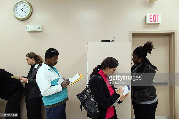 Paula Lobo and others fill out job applications as they attend the Village at Gulfstream Park job fair on January 12 2010 in Hallandale Florida The...