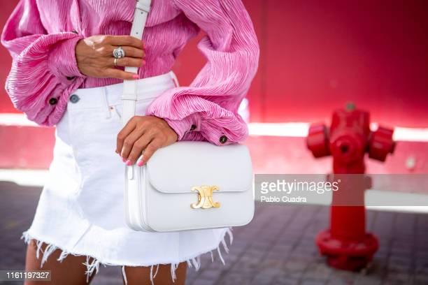 Paula Ordovas wears Ganni shirt, Levis skirt, Celine handbag, Jimmy Choo shoes, Mercedes Salazar earings and Gigi Barcelona sunglasses during...