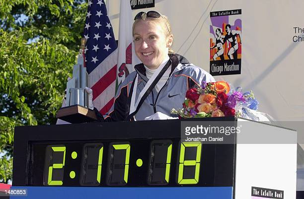Paula Radcliffe of England poses on the winners stand in front of her world record time of 21718 after winning the Chicago Marathon on October 13...