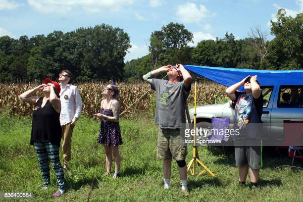 Paula Robinson Chris Tupp Dabnie James James Neal and Jack Cook use eclipse glasses to watch the beginning of the solar eclipse on August 21 2017
