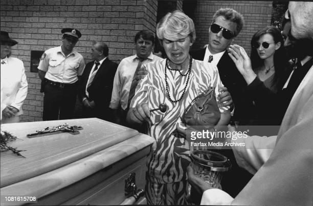 Paulas sister Patricia Sprinkles water on the coffin of her sisterRichard Dickin Paulas Defacto comforts her January 13 1994