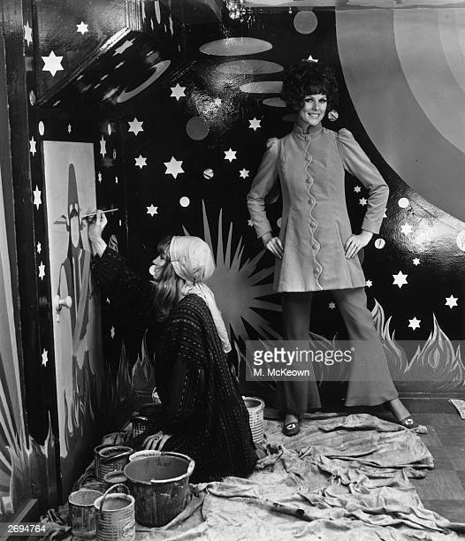 Paulene Stone models a velvet coat price 16 guineas from Apple Boutique while at her feet a young woman surrounded by tins of paint and dust sheets...