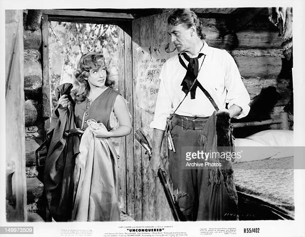 Paulette Goddard and Gary Cooper looking at each other at doorway in a scene from the film 'Unconquered' 1947