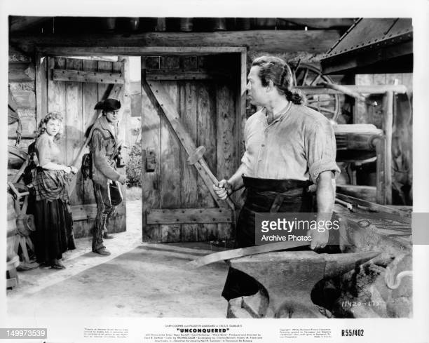 Paulette Goddard and Gary Cooper looking at man hammering metal as they walk out in a scene from the film 'Unconquered' 1947