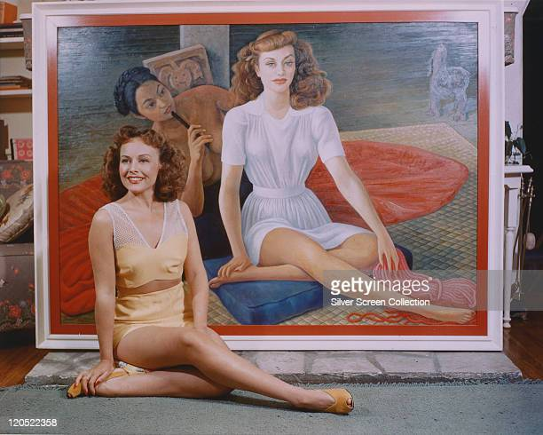 Paulette Goddard US actress sitting on the floor alongside a portrait of herself painted by the Mexican artist Diego Rivera circa 1940 The portrait...