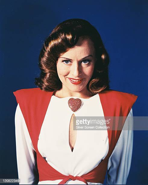 Paulette Goddard , US actress, wearing a red-and-white blouse, with a keyhole neckline, and a large red heart-shaped brooch in a studio portrait,...