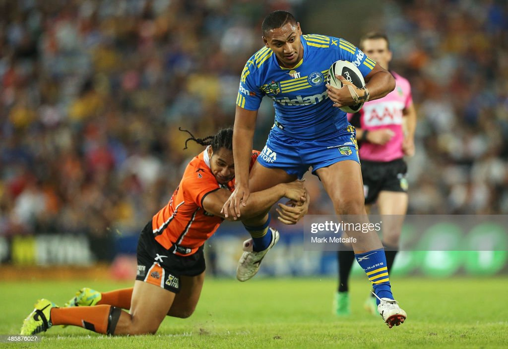 Pauli Pauli of the Eels evades is tackled by Martin Taupau of the Tigers during the round seven NRL match between the Parramatta Eels and the Wests Tigers at ANZ Stadium on April 21, 2014 in Sydney, Australia.