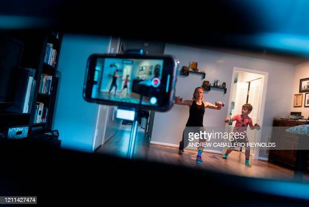 TOPSHOT Paulina Mansz a group fitness instructor mimicked by her son Daniel records a workout session for her clients as she continues to instruct...