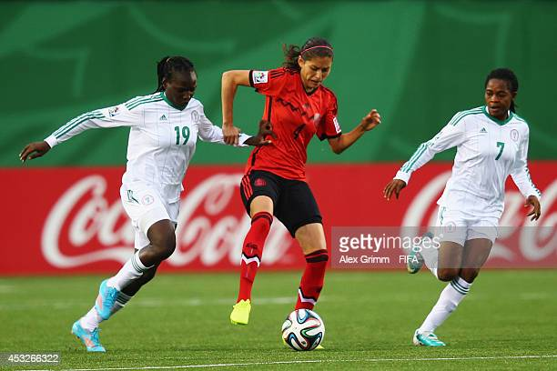 Paulina Solis of Mexico is challenged by Chinwendu Ihezuo and Loveth Ayila of Nigeria during the FIFA U20 Women's World Cup Canada 2014 group C match...