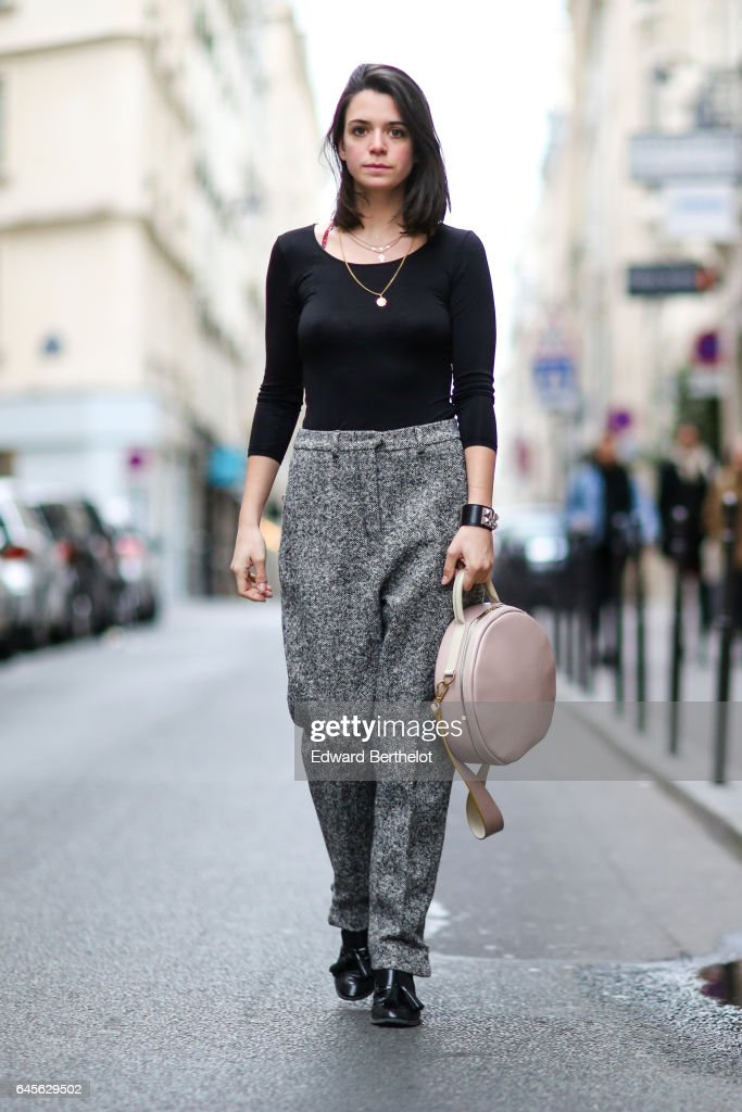Pauline Darris, Founder of the accessories brand Darris, wears a Uniqlo black top, Saint Laurent YSL wool gray pants, a Hermes bracelet, a Darris Paris pink bag, and Zara balck shoes, on February 26, 2017 in Paris, France.