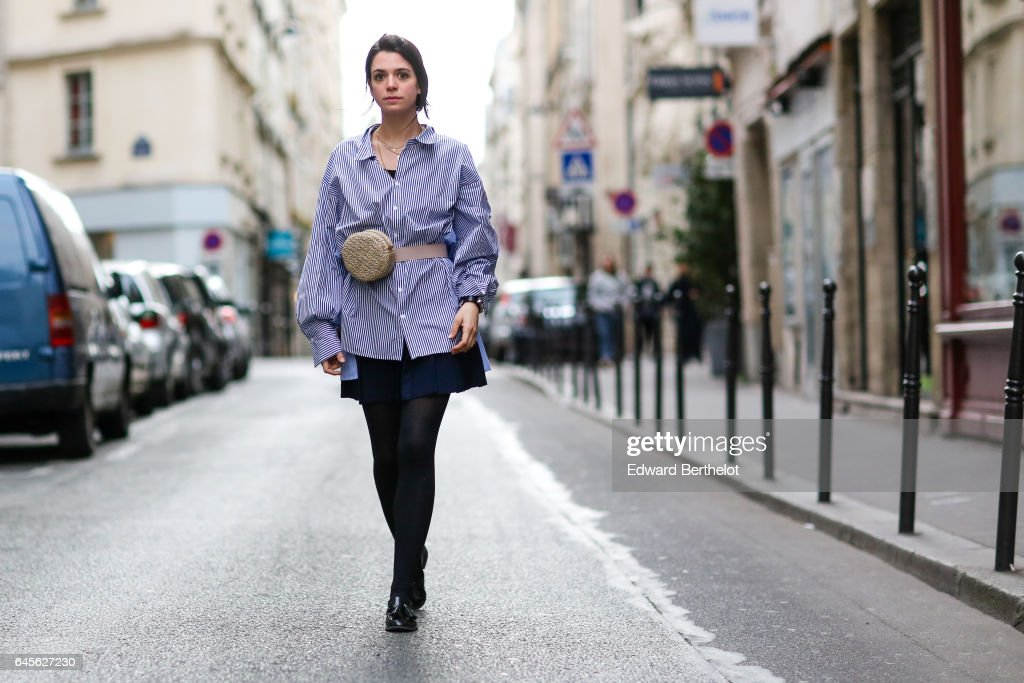 Pauline Darris, Founder of the accessories brand Darris, wears a Zara striped shirt, an American Apparel blue skirt, Zara black shoes, a Hermes bracelet, and a Darris Paris 'Banane Raphias' bag, on February 26, 2017 in Paris, France.