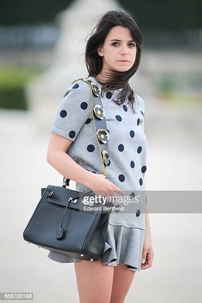 Pauline Darris is wearing a Vanessa Bruno dress, a Hermes Kelly bag, a Darris bag handle, Converse shoes, and a Darris shoe tongue, during a street...