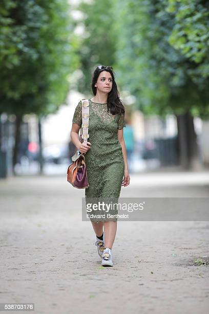 Pauline Darris is wearing a Zara green dress a Saint Laurent bag a Darris bag handle Converse white shoes and a Darris shoe tongue during a street...