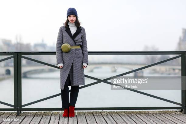 Pauline Darris wears a Cos blue beanie hat an Eric Bompard pull over a Zara coat Levi's 501 vintage jeans Topshop red boots and a Darris green bag at...