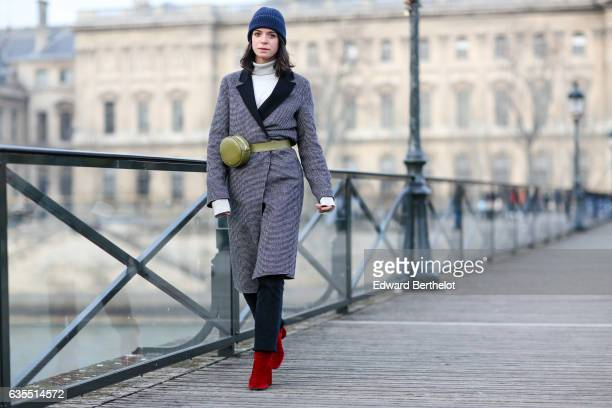 Pauline Darris wears a Cos blue beanie hat, an Eric Bompard pull over, a Zara coat, Levi's 501 vintage jeans, Topshop red boots, and a Darris green...
