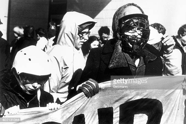 Pauline McKay Chairperson of HART marches behind a banner with antiapartheid demonstrator wearing baseball helmet and cricket gloves towards rugby...