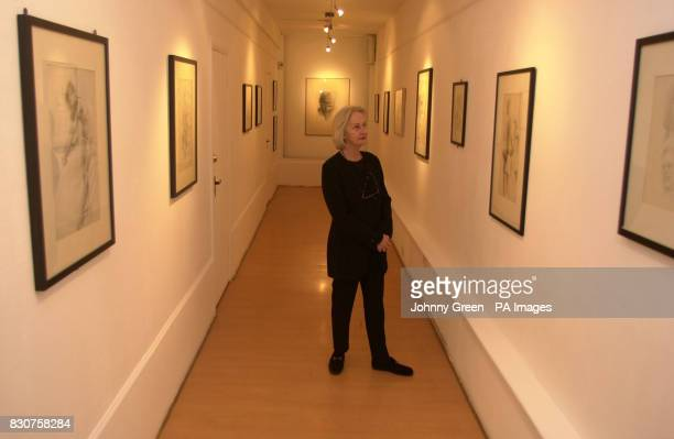 Pauline Sutcliffe the sister of the man known as the fifth Beatle Stuart Sutcliffe stands beside photographs of Stuart and the band taken by his then...