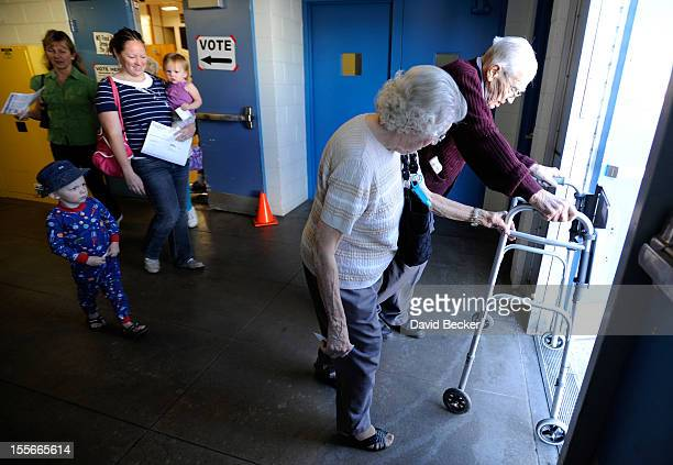 Pauline Vallee helps Robert Krack exit the polling station after casting his ballot at John Fremont Middle School on November 6 2012 in Las Vegas...