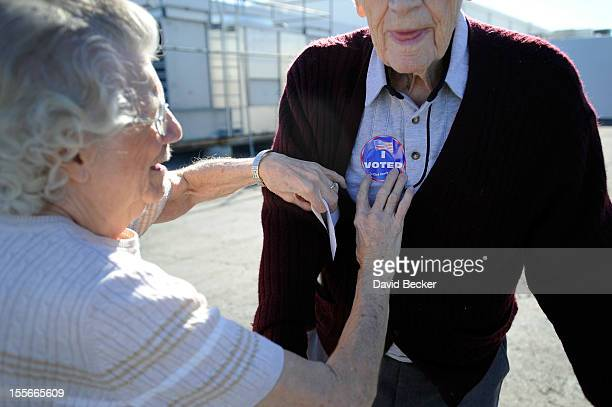 Pauline Vallee helps Robert Krack with his I Voted sticker after casting his ballot at the polling station at John Fremont Middle School on November...