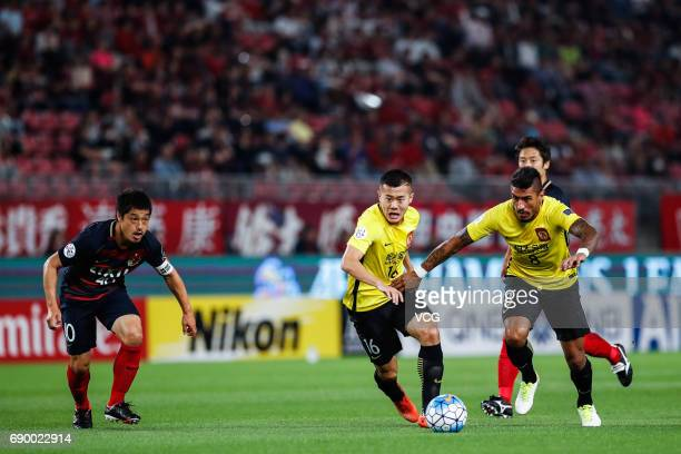 Paulinho and Huang Bowen of Guangzhou Evergrande and Mitsuo Ogasawara of Kashima Antlers vie for the ball during the AFC Champions League Round of 16...