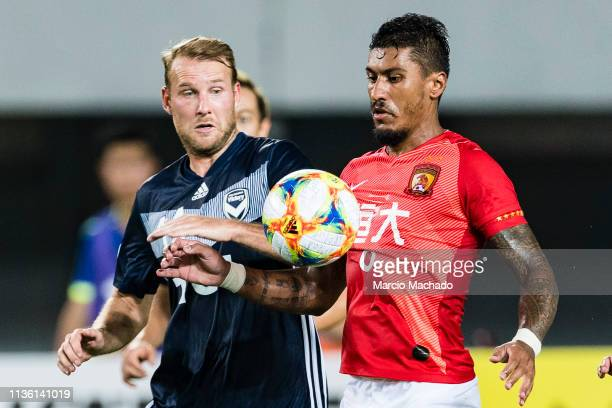 Paulinho Maciel of Guangzhou fights for the ball with Ola Toivonen of Melbourne during the Match Day 3 of Asia Champions League Group Stage F, match...