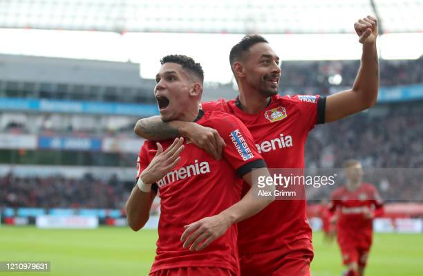 Paulinho of Bayer 04 Leverkusen celebrates with teammate Karim Bellarabi after scoring their team's fourth goal during the Bundesliga match between...