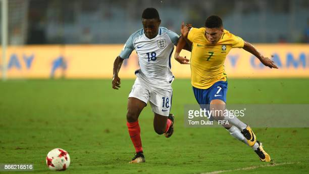 Paulinho of Brazil and Steven Sessegnon of England in action during the FIFA U17 World Cup India 2017 Semi Final match between Brazil and England at...