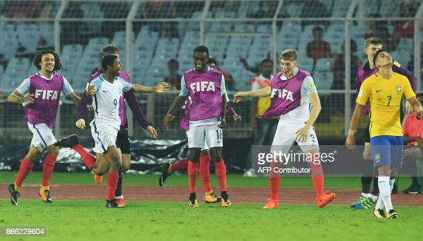 Paulinho of Brazil reacts as Rhian Brewster of England celebrates after scoring the second goal during the semifinal football match in the FIFA U17...