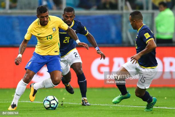 Paulinho of Brazil struggles for the ball with Gabriel Achilier and Pedro Quinonez of Ecuador during a match between Brazil and Ecuador as part of...