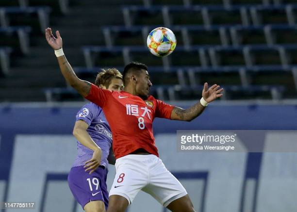 Paulinho of Guangzhou Evergrande and Sho Sasaki of Sanfrecce Hiroshima compete for the ball during the AFC Champions League Group F match between...
