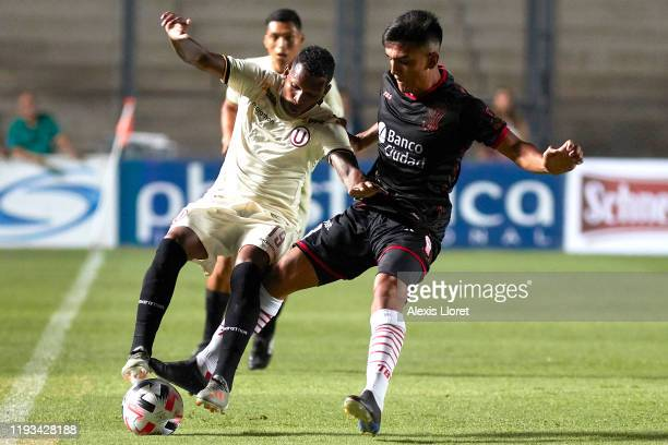 Paulo de la Cruz of Universitario competes for the ball with Nicolás Romat of Huracán during a friendly match between Huracan and Universitario...
