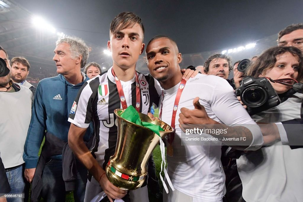 Paulo Dybala and Douglas Costa of Juventus celebrate with the trophy after winning the TIM Cup Final between Juventus and AC Milan at Stadio Olimpico on May 9, 2018 in Rome, Italy.