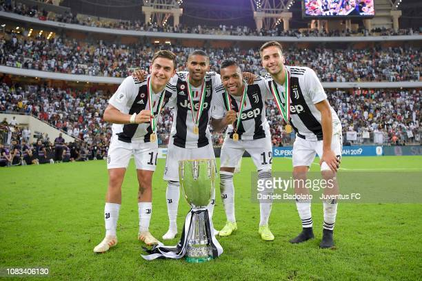 Paulo Dybala Douglas Costa Alex Sandro and Rodrigo Bentancur of Juventus celebrate with trophy after winning the Italian Supercup match between...