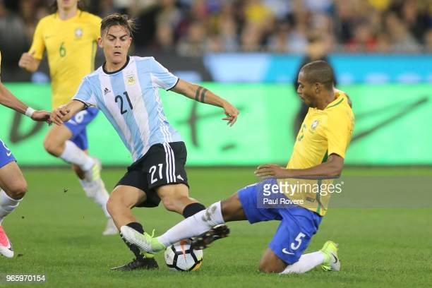 Paulo Dybala of Argentina competes for the ball with Fernandinho of Brazil during the Brazil Global Tour match between Brazil and Argentina at...