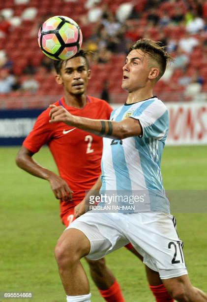 Paulo Dybala of Argentina competes for the ball with Mohamad Izwan Mahbud of Singapore during their international friendly football match at the...