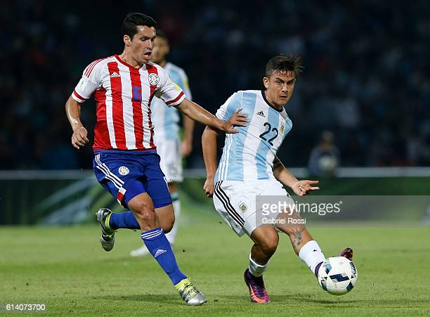 Paulo Dybala of Argentina fights for the ball with Cristian Riveros of Paraguay during a match between Argentina and Paraguay as part of FIFA 2018...
