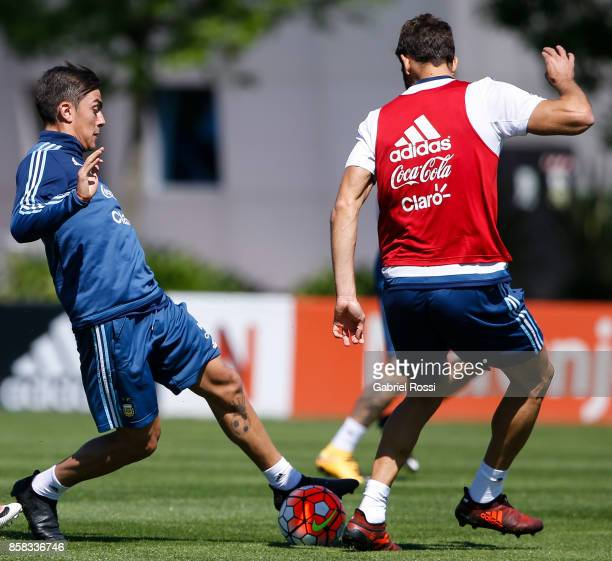 Paulo Dybala of Argentina fights for the ball with Federico Fazio of Argentina during a training session at Argentine Football Association 'Julio...