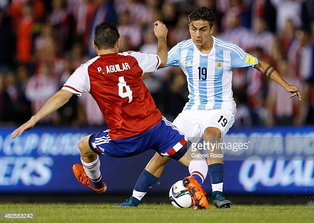 Paulo Dybala of Argentina fights for the ball with Pablo Aguilar of Paraguay during a match between Paraguay and Argentina as part of FIFA 2018 World...