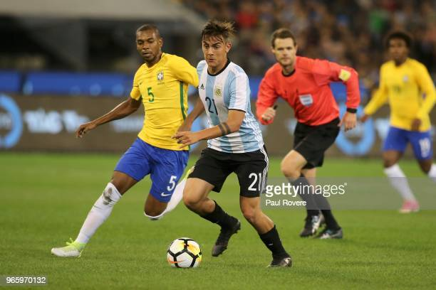 Paulo Dybala of Argentina leads Fernandinho of Brazil to the ball during the Brazil Global Tour match between Brazil and Argentina at Melbourne...