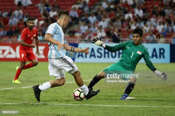 Paulo Dybala of Argentina tries to shoot past Izwan Mahbud of Singapore during the International Test match between Argentina and Singapore at...