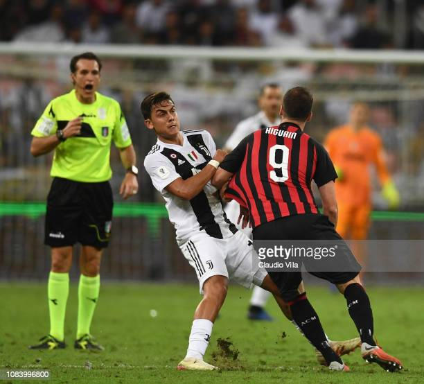 Paulo Dybala of Juventus and Gonzalo Higuain of AC Milan compete for the ball during the Italian Supercup match between Juventus and AC Milan at King...
