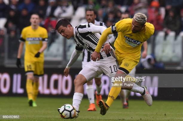 Paulo Dybala of Juventus and Valon Behrami of Udinese compete for the ball during the serie A match between Juventus and Udinese Calcio on March 11...