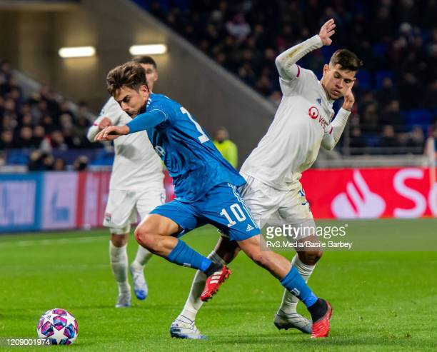 Paulo Dybala of Juventus battles for the ball with Bruno Guimaraes of Olympique Lyonnais during the UEFA Champions League round of 16 first leg match...