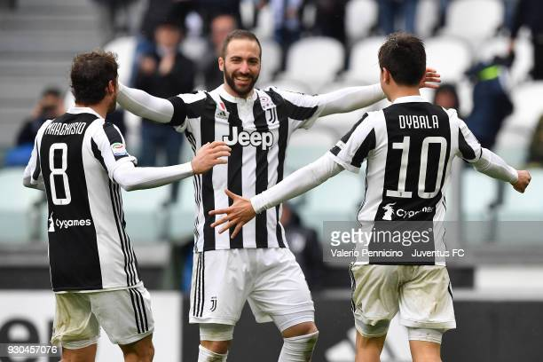 Paulo Dybala of Juventus celebrates his goal of 20 with teamates Claudio Marchisio and Gonzalo Higuain during the serie A match between Juventus and...