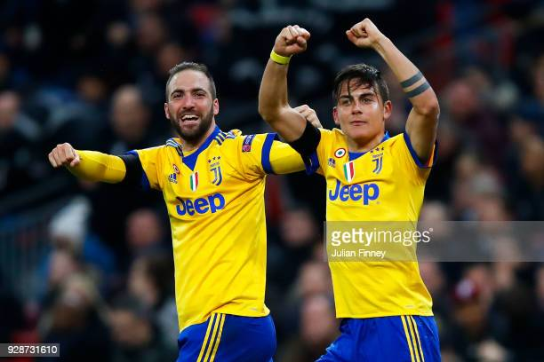 Paulo Dybala of Juventus celebrates with his team mate Gonzalo Higuain after scoring his team's second goal during the UEFA Champions League Round of...