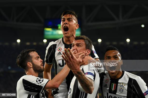 Paulo Dybala of Juventus celebrates with Miralem Pjanic, Mario Mandzukic and Alex Sandro of Juventus after scoring his team's second goal during the...
