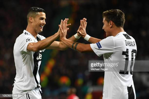 Paulo Dybala of Juventus celebrates with teammate Cristiano Ronaldo after scoring his team's first goal during the Group H match of the UEFA...